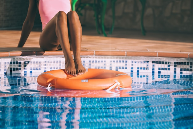 Woman legs in a swimming pool with lifesaver
