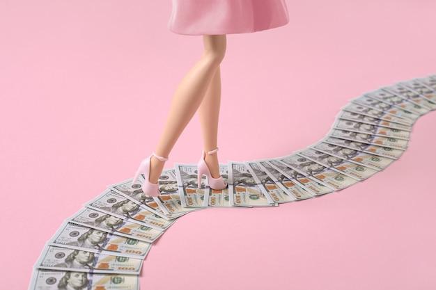 女性の足は、ピンクの背景にお金の道、ドル紙幣の道に沿って歩きます。