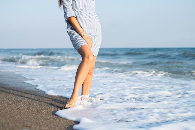 해변에서 걷는 여자 다리. 고품질 사진