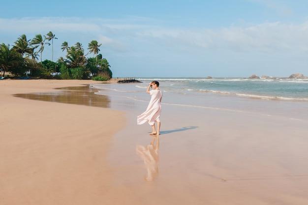 Ноги женщины гуляя на песок пляжа