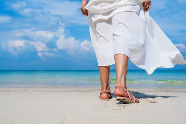 Ноги женщины гуляют на берегу моря на острове ко мун-норк, районг, таиланд