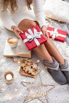 Ноги женщины с рождественскими носками и подарками.