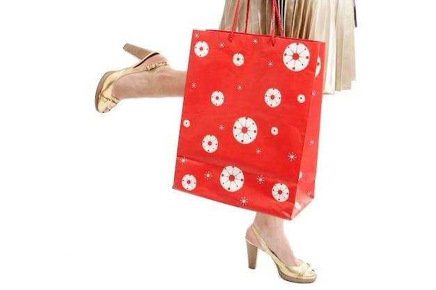 Ноги женщины с пакетом бегают по магазинам на белом