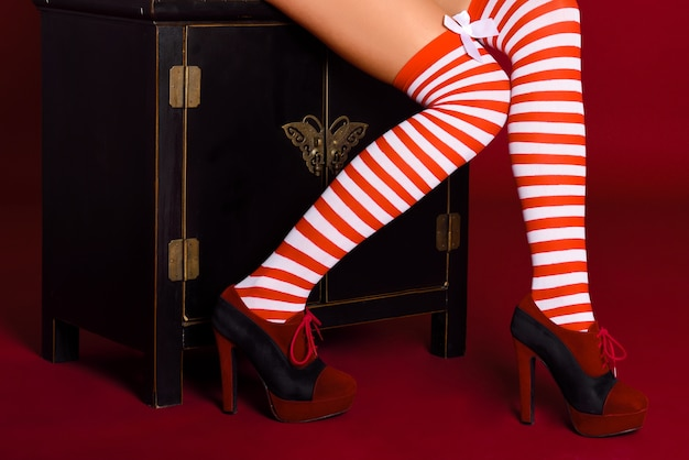Woman legs with red and white striped tights on red background