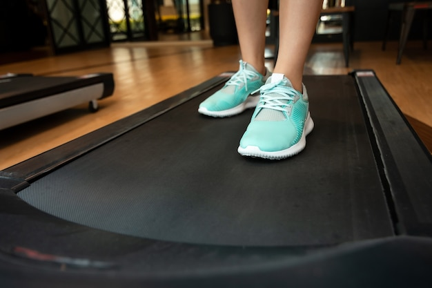 Woman legs with sport shoes running on treadmill in fitness gym.