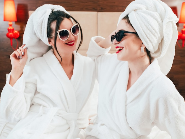 女性の余暇。美容ライフスタイル。サングラス、バスローブ、ターバンを着た2人の笑顔の女性。楽しさと喜びの時間。