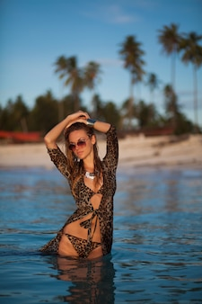 Woman in leopard print dress and swimsuit on the tropical beach