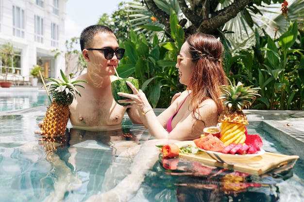 Woman letting her boyfriend to try watermelon cocktail
