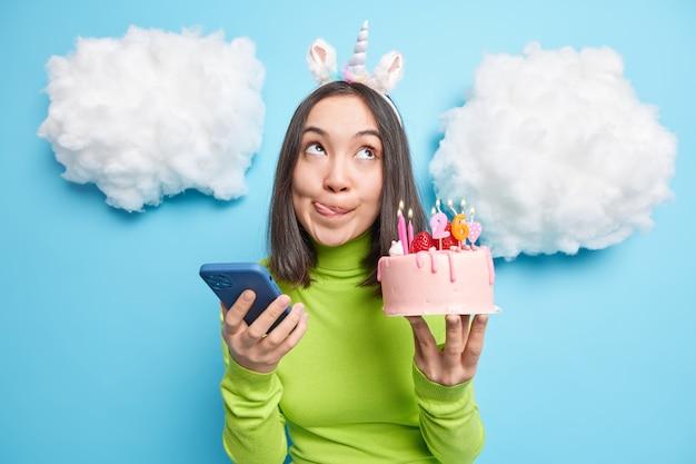 女性は唇をなめる 燃えるろうそくでおいしいケーキを持って 26歳の誕生日を祝う 携帯電話スタンドでお祝いのメッセージを受け取る
