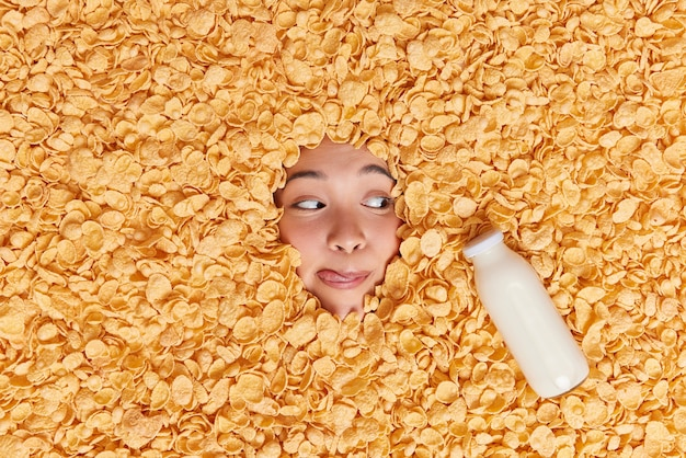 Woman licks lips looks at milk bottle buried in flakes going to have breakfast keeps to healthy nutrition