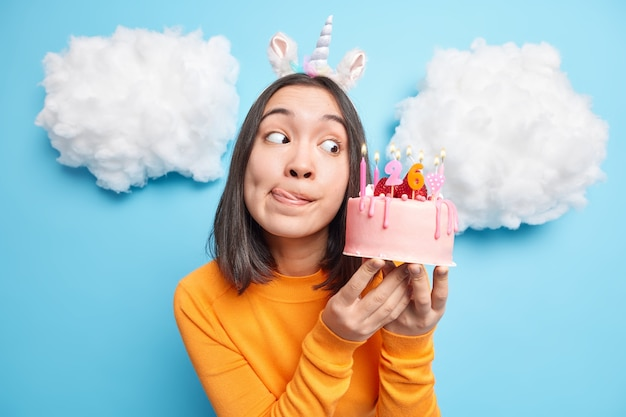 Woman licks lips looks with temptation at tasty birthday cake going to make wish while blowing candles dressed in orange jumper isolated on blue