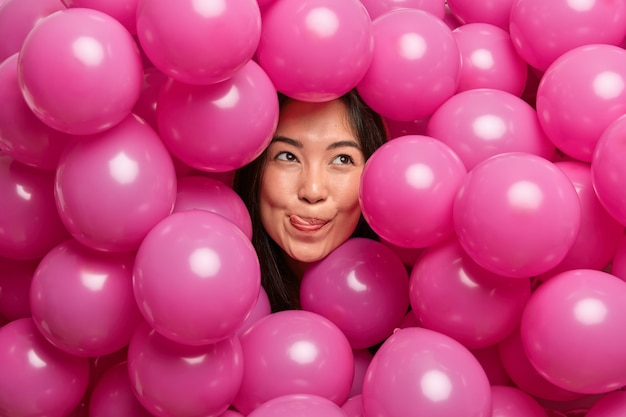 Woman licks lips with tongue concentrated above thoughtfully surrounded with inflated pink balloons