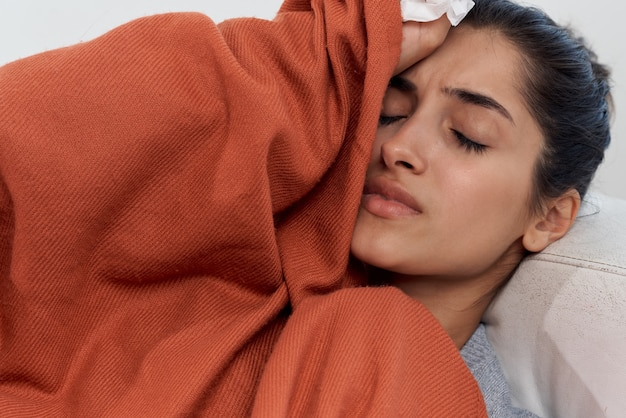 女性は目を閉じて冷たい毛布で覆われたソファの上に家に横たわっています
