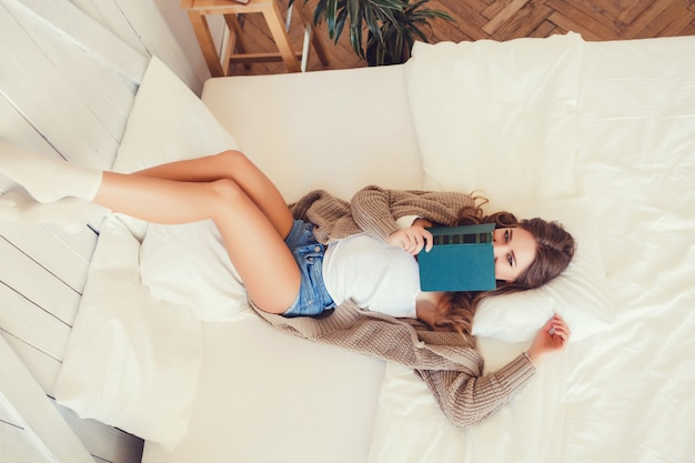 Woman lies on a bed with a book