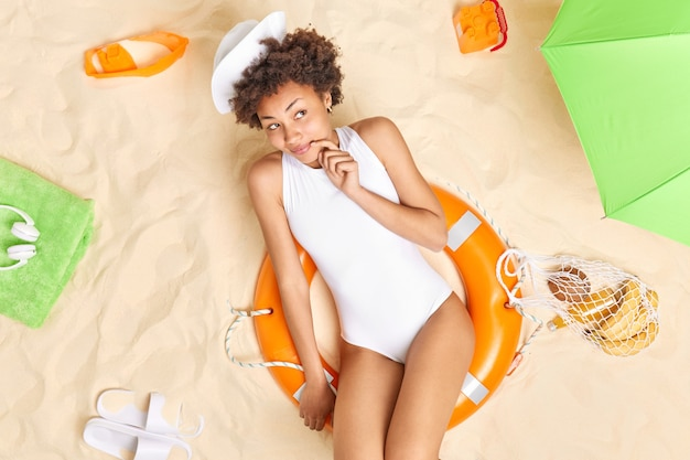 Woman lies down on lifebuoy at sand rests during summer vacation wears white hat and bikini sunbathes in tropical beach. recreation rest lifestyle concept