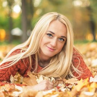 女性は秋の公園の葉に横になります
