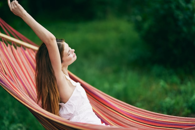 A woman lies in a hammock in nature and is resting