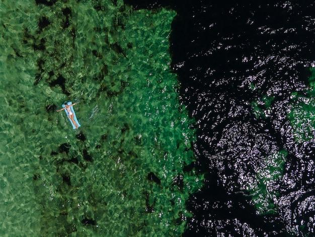 Женщина лежит в серебряном купальнике на синем надувном матрасе в море