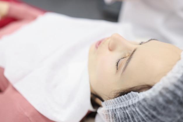 Женщина лежит в салоне красоты перед омолаживающей процедурой, концепция офиса косметолога