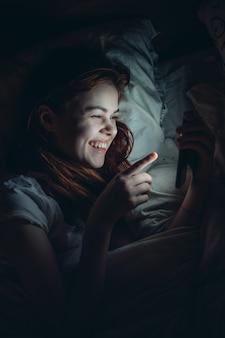 女性はコミュニケーションの感情を手に電話で夜ベッドに横たわっています