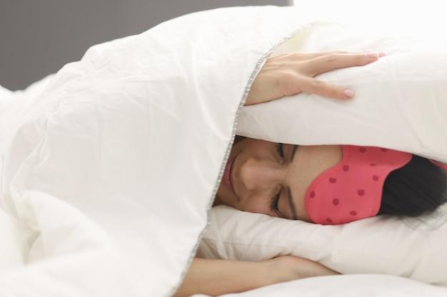 여자는 밤 컨셉에서 담요 불면증과 주변 소음으로 머리를 덮고 침대에 누워 있다