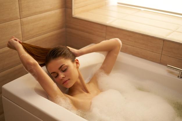 Женщина лежит в ванной с белой пеной, закрытыми глазами расслабиться