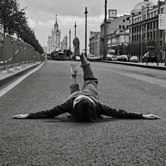 Женщина лежит на пустой асфальтовой дороге с поднятыми ногами.