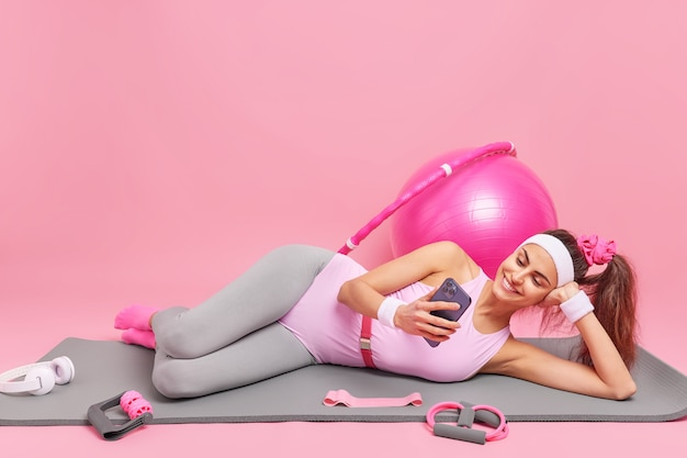 Женщина лежит на удобном коврике для фитнеса, смотрит видео через смартфон, одетая в спортивную одежду, упражнения со спортивным оборудованием