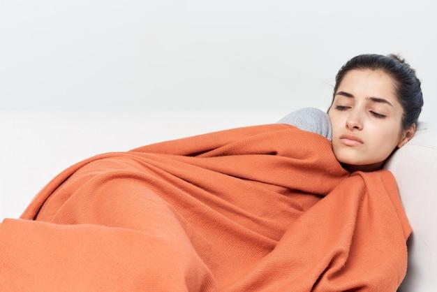 女性は毛布の冷たい治療で覆われたベッドに横たわっています