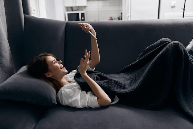 Женщина лежит на диване с телефоном в руке, вид сбоку, комфорт интерьера. фото высокого качества
