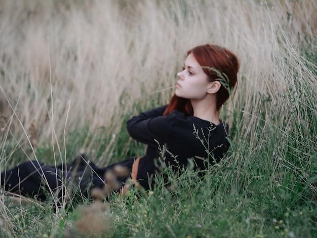 女性はフィールド休息の自由の自然の草の上に横たわっています