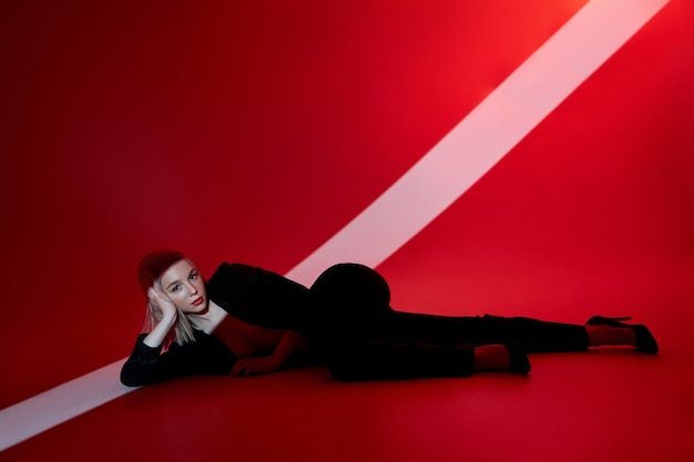 Woman lies on red background with ray of light on face. sexy nude and confident blonde woman in black jacket. red light
