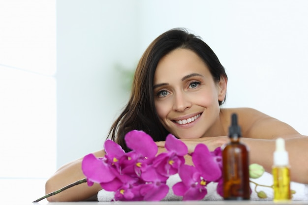 Woman lies and smiles in massage room closeup