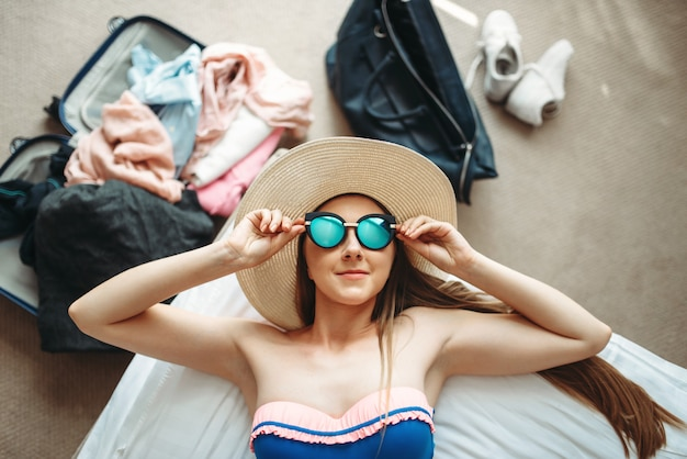 Woman lies in swimsuit and sunglasses, top view