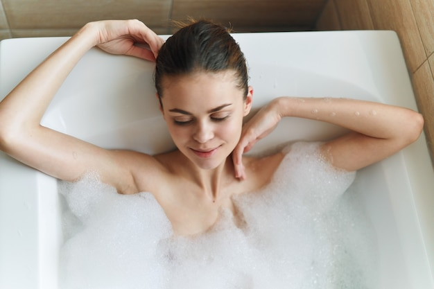 Woman lies in a white bath clean skin white foam spa procedures