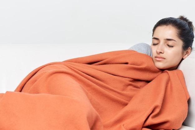 女性は毛布の冷たい治療で覆われた目を閉じて横たわっています