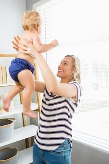 Женщина поднимая ребенка и улыбается