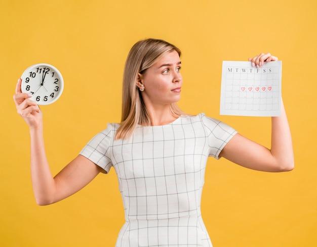 Женщина поднимает часы и календарь