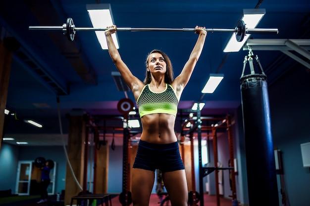 Женщина, поднятие тяжестей crossfit в тренажерном зале. фитнес женщина тяги штанги