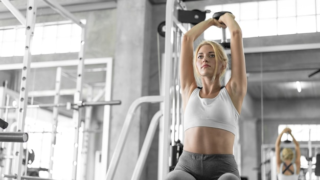 Woman lifting dumbbell in gym health and fitness concept