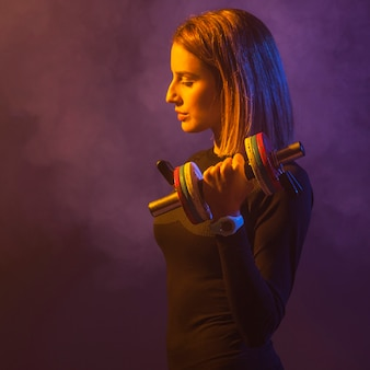 Woman lifting dumbbell in smoke
