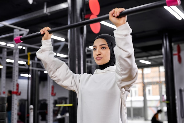 現代のフィットネスジムでのスポーツトレーニングトレーニング中に空のバーベルを持ち上げる女性。健康的なライフスタイルとスポーツ、アラビア語のスポーツの概念