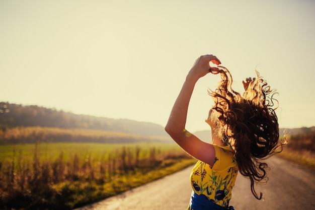 Woman lifting her hair with a road in the background
