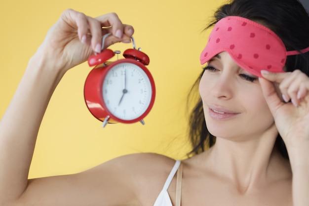 눈에서 수면 마스크를 들고 빨간 알람 시계를 보고 있는 여자. 근무 시간 일정 개념