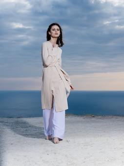 Woman in light clothes by the ocean and blue sky in the background