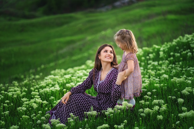 Woman in light clothes have fun with cute child baby girl