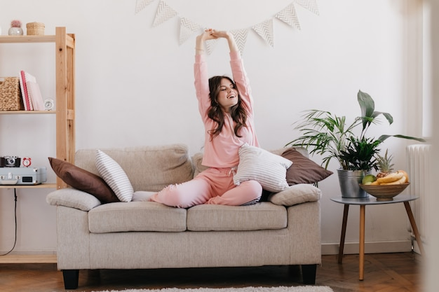 Woman in light pink pajamas raises her hands up after good sleep and poses in apartment
