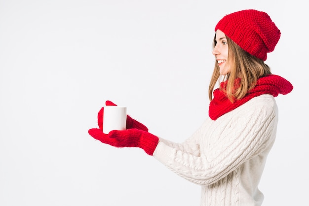 Woman in light sweater holding cup