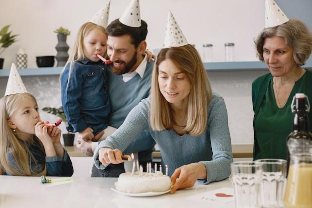 La donna accende le candele sulla torta di compleanno l'anziana e il figlio adulto restano indietro