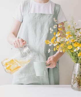 Woman in linen apron drinking lemonade with cozy home